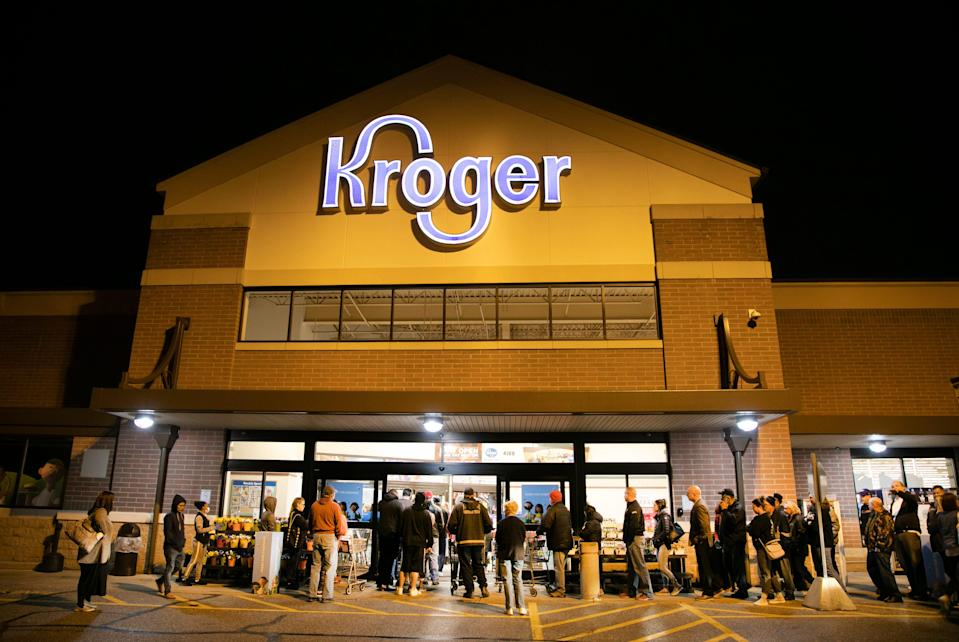 People are lined up at a Kroger in Blue Ash, Ohio, as the doors open at 7 a.m. March 17, 2020. Because of high demand and the need for restocking and cleanliness, the chain reduced hours.