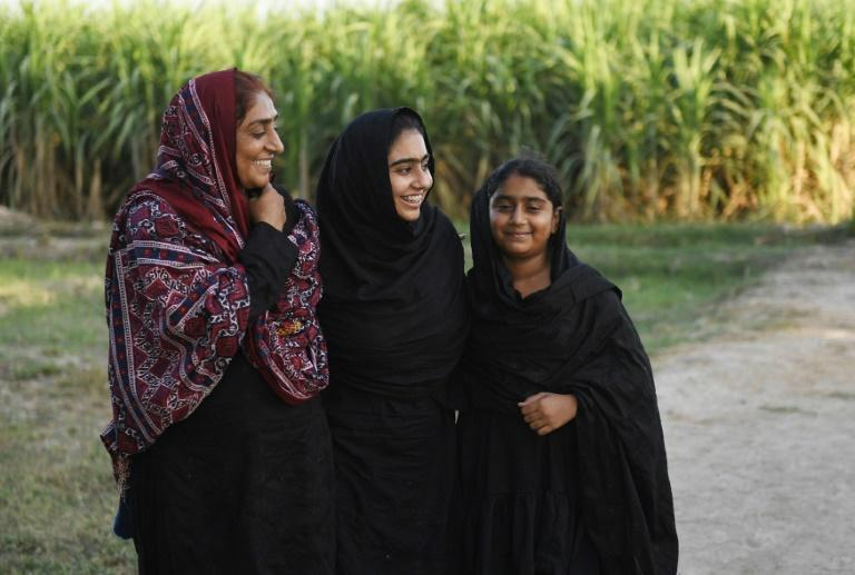 Pakistani woman Mukhtiar Naz (L), known as Waderi Nazo Dharejo, with her daughters at her agriculture field in Qazi Ahmed in Sindh province