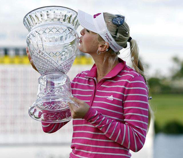 Jessica Korda of the U.S. kisses her trophy as she poses for photographers following her victory at the LPGA Pure Silk Bahamas Classic at the Ocean Club Golf Course, Paradise Island, Bahamas, Sunday, Jan. 26, 2014. (AP Photo/Tim Aylen)