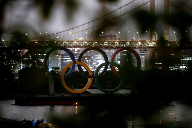 The giant Olympic rings are seen through a tree in Tokyo