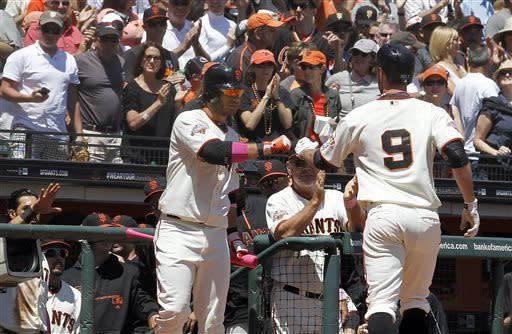 San Francisco Giants shortstop Brandon Crawford, front left, congratulates Brandon Belt (9) who hit a solo home run against the Atlanta Braves during the second inning of a baseball game in San Francisco, Sunday, May 12, 2013. (AP Photo/Tony Avelar)