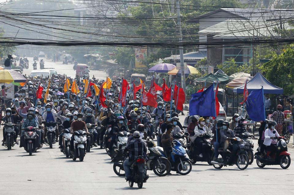 """Protesters carry flags as they drive their motorcycles during an anti-coup protest in Mandalay, Myanmar on Thursday March 25, 2021. Protesters against last month's military takeover in Myanmar returned to the streets in large numbers Thursday, a day after staging a """"silence strike"""" in which people were urged to stay home and businesses to close for the day. (AP Photo)"""