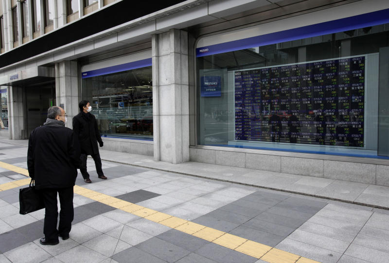 Men watch an electric stock price indicator in Tokyo, Wednesday, Jan. 16, 2013. Japan's benchmark index toppled off a 32-month high Wednesday after its currency's downward slide went into reverse. (AP Photo/Shizuo Kambayashi)