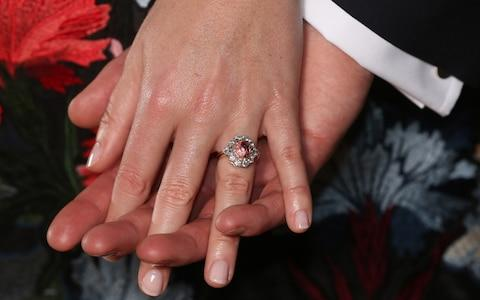 Princess Eugenie wears a ring containing a padparadscha sapphire surrounded by diamonds  - Credit: Jonathan Brady /PA