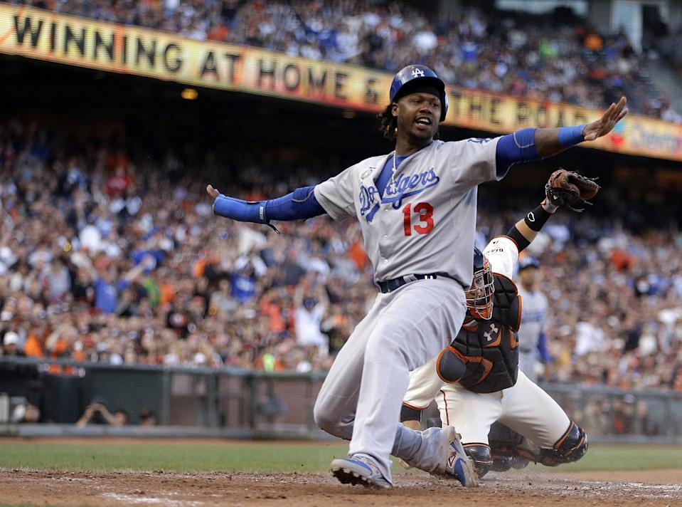 FILE - In this July 27, 2014, file photo, Los Angeles Dodgers' Hanley Ramirez (13) signals he is safe after scoring past San Francisco Giants catcher Buster Posey in the fifth inning of a baseball game in San Francisco. The Boston Red Sox expect to finalize the signing of Ramirez on Tuesday, Nov. 25, 2014. (AP Photo/Ben Margot, File)