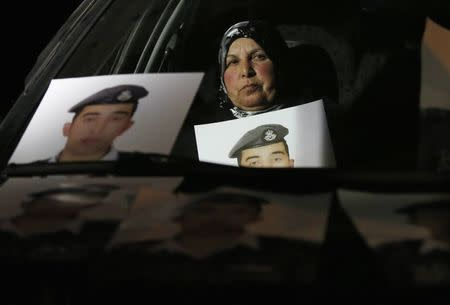 Mother of Islamic State captive Jordanian pilot Muath al-Kasaesbeh holds his picture while sitting in a car, as she takes part in a demonstration demanding that the Jordanian government negotiate with Islamic state and for the release of her son, in front of the prime minister's building in Amman, January 27, 2015. REUTERS/Muhammad Hamed