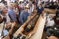 Khaled El-Enaby, Minister of Tourism and Antiquities, right, and Mostafa Waziri, the secretary-general of the Supreme Council of Antiquities, left, react after opening the sarcophagus is around 2500 years old at the Saqqara archaeological site, 30 kilometers (19 miles) south of Cairo, Egypt, Saturday, Oct. 3, 2020. Egypt says archaeologists have unearthed about 60 ancient coffins in a vast necropolis south of Cairo. The Egyptian Tourism and Antiquities Minister says at least 59 sealed sarcophagi with mummies inside were found that had been buried in three wells more than 2,600 years ago. (AP Photo/Mahmoud Khaled)