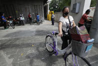 A recipient of a bicycle from the Benjamin Canlas Courage to be Kind Foundation pushes her bicycle outside a building at the financial district of Manila, Philippines, Saturday, July 11, 2020. Restricted public transportation during the lockdown left many Filipinos walking for hours just to reach their jobs. The foundation saw the need and gave away mountain bikes to nominated individuals who are struggling to hold on to their jobs in a country hard hit by the coronavirus. (AP Photo/Aaron Favila)