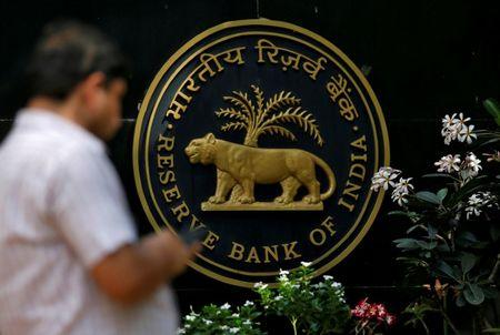 FILE PHOTO: A man checks his phone outside the RBI headquarters in Mumbai