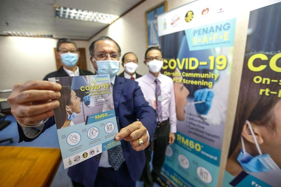 Penang exco Jagdeep Singh Deo holds up a brochure on mass Covid-19 screening during a press conference at Komtar, George Town December 24, 2020. — Picture by Sayuti Zainudin