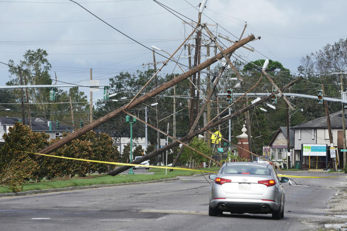 A car drives toward fallen utility poles wth yellow tape stretched across the street.