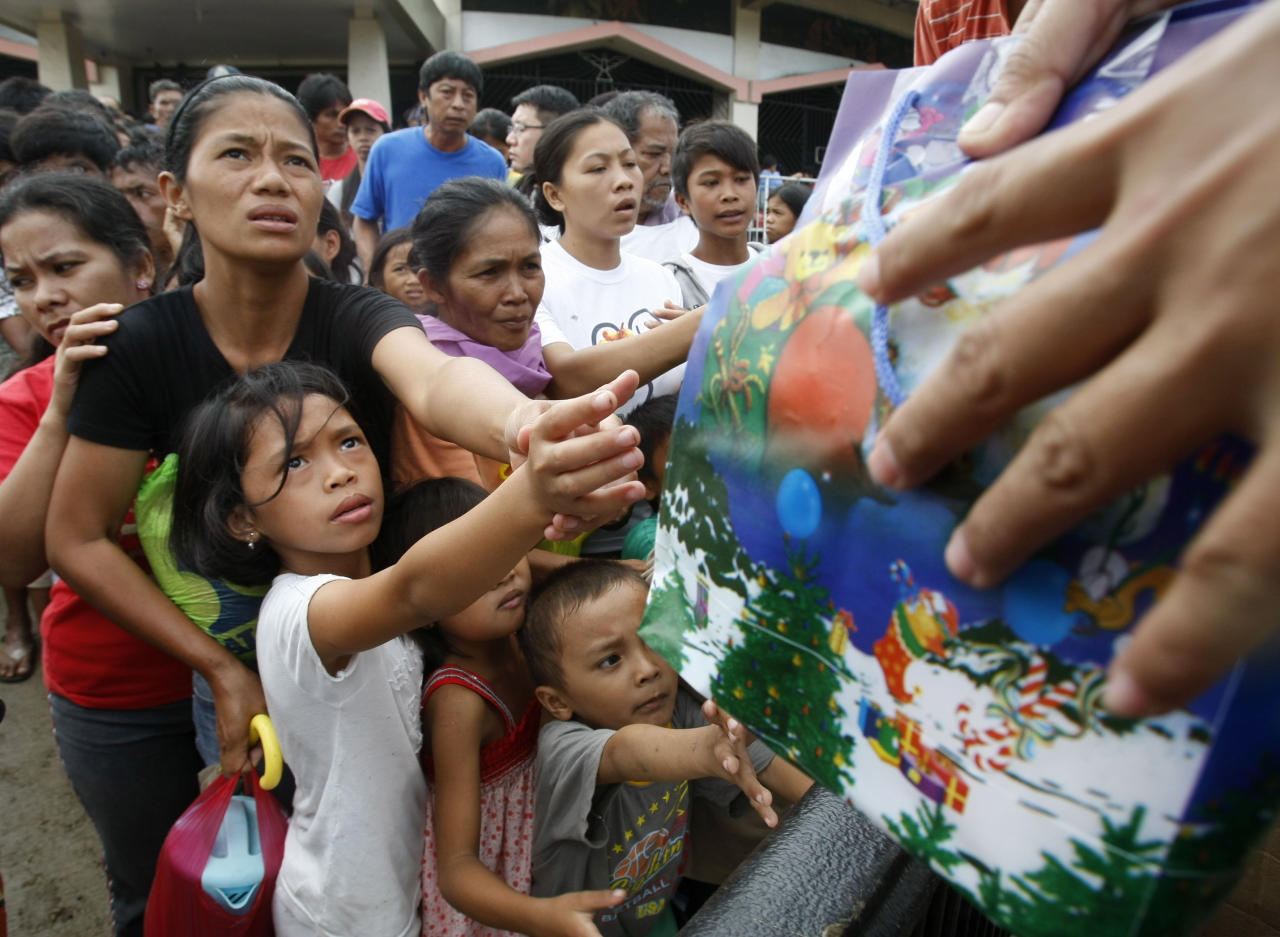 Residents queue up for relief supplies at an evacuation center Monday, Dec. 19, 2011 in Iligan city, southern Philippines. Tropical storm Washi blew away Monday after devastating the southern Philippines with flash floods that killed hundreds of people as they slept and turned two coastal cities into a muddy wasteland filled with overturned cars and uprooted trees. (AP Photo/Bullit Marquez)