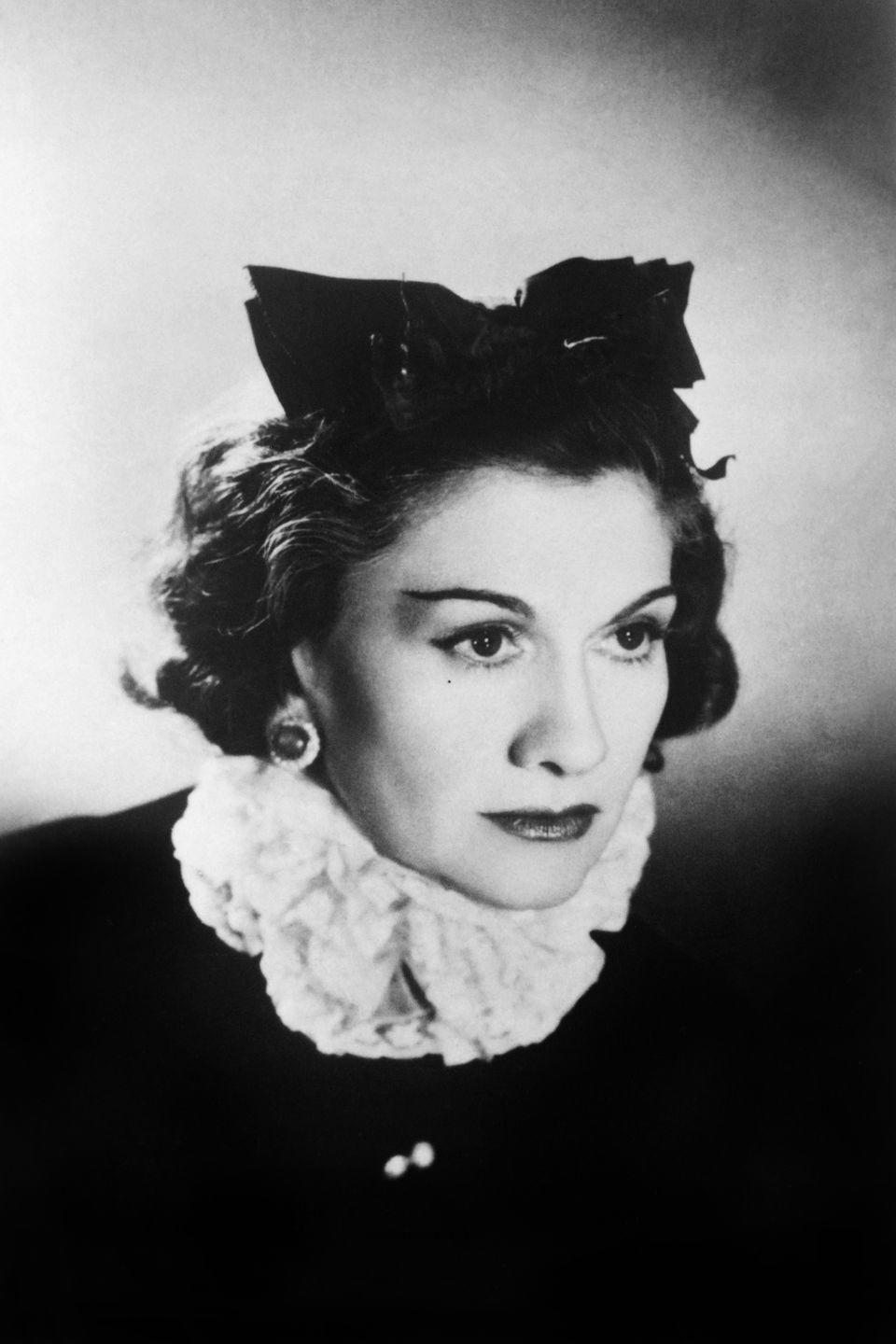 <p>Coco Chanel poses for a portrait wearing a ruffled collar and bow in her hair.</p>