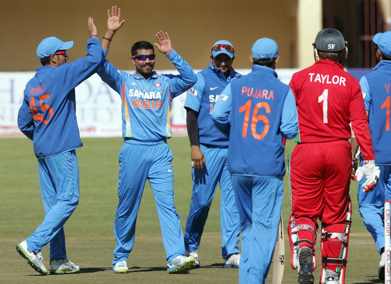 Indian players congratulate team mate Ravindra Jadeja (2nd L) after he claimed the wicket of Zimbabwe's captain during the 4th match of the 5-match cricket ODI series between Zimbabwe and India at Queen's Sports Club in Harare on August 1, 2013. AFP PHOTO / Jekesai Njikizana        (Photo credit should read JEKESAI NJIKIZANA/AFP/Getty Images)