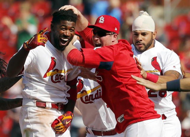St. Louis Cardinals' Dexter Fowler, left, is congratulated by teammates Jedd Gyorko and Tommy Pham, right, after hitting a walkoff single during the 13th inning of a baseball game against the New York Mets, Thursday, April 26, 2018, in St. Louis. (AP Photo/Jeff Roberson)