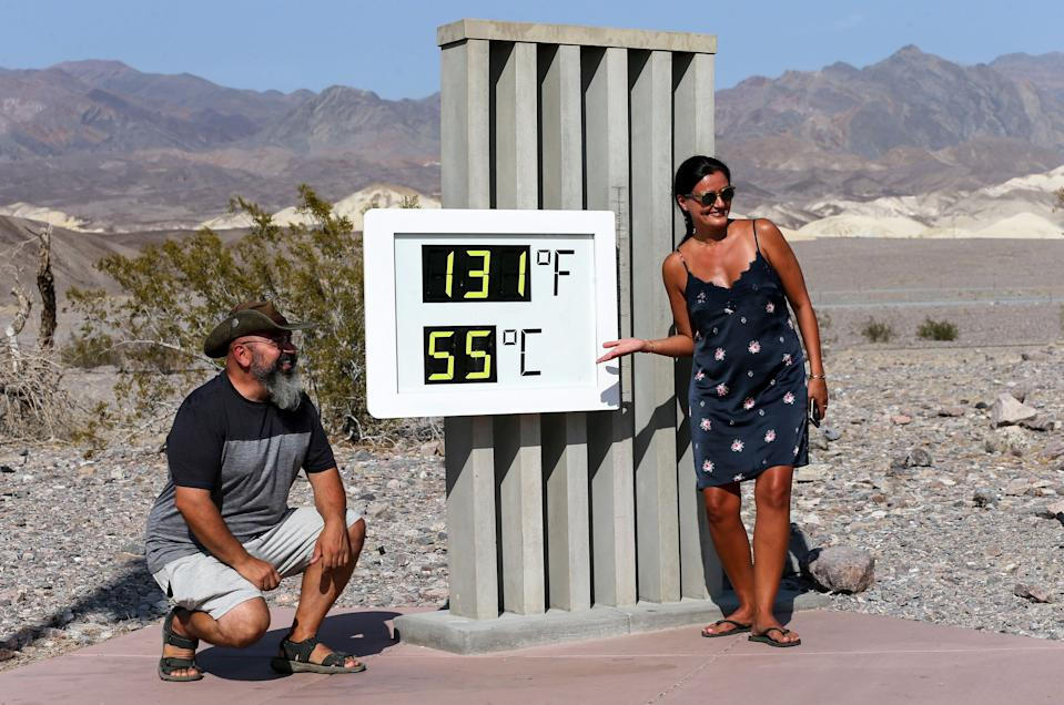DEATH VALLEY NATIONAL PARK, CALIFORNIA - AUGUST 17: Visitors gather for a photo in front of an unofficial thermometer at Furnace Creek Visitor Center on August 17, 2020 in Death Valley National Park, California. The temperature reached 130 degrees at Death Valley National Park on August 16, hitting what may be the hottest temperature recorded on Earth since at least 1913, according to the National Weather Service. Park visitors have been warned, 'Travel prepared to survive.' (Photo by Mario Tama/Getty Images)