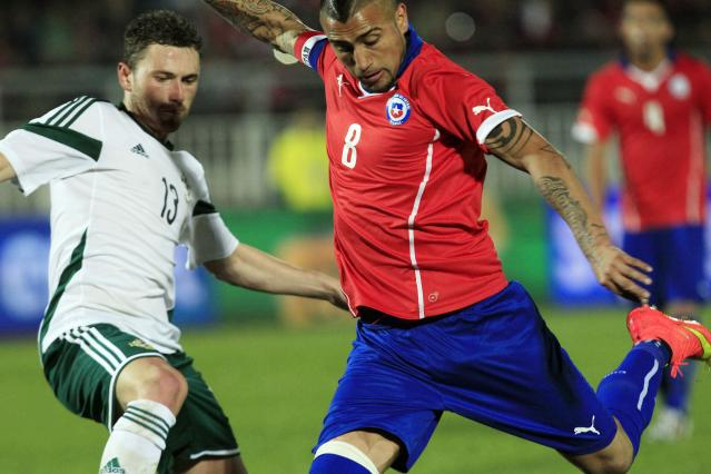 Chile's Arturo Vidal, battles for the ball against Northern Ireland's Cory Evans, during an international friendly soccer match in Valparaiso, Chile, Wednesday, June 4, 2014. (AP Photo/Luis Hidalgo)