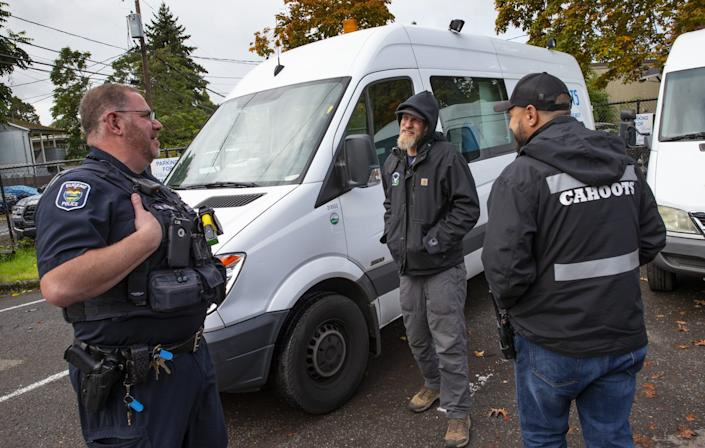 Eugene Police officer Bo Rankin, left, meets with Cahoots administrative coordinator Ben Brubaker and emergency crisis worker Matt Eads, right, after working a shift together as part of the Community Outreach Response Team in Eugene.