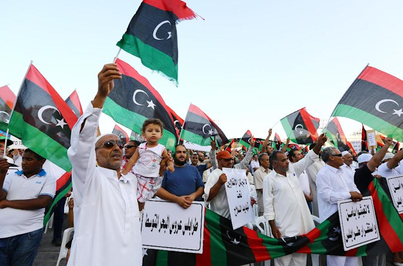 Libyans wave national flags and hold placards during a protest against the new anti-Islamist parliament on August 15, 2014 Tripoli (AFP Photo/Mahmud Turkia)