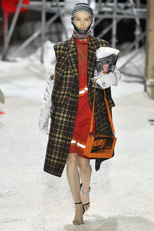 <p>A model wears a houndstooth sleeveless coat over an orange safety dress, a balaclava, and scrunched opera gloves while carrying a bag of popcorn at the Calvin Klein fall 2018 show. (Photo: Getty Images) </p>