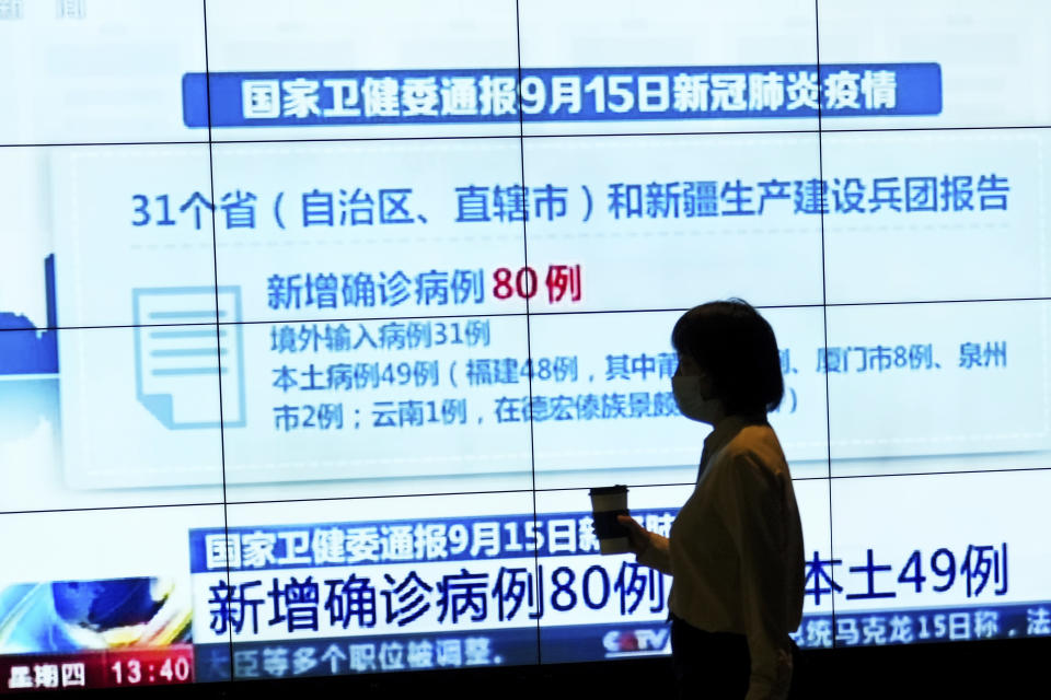 A woman wearing a face mask to help curb the spread of the coronavirus is silhouetted as she walks by a TV screen showing CCTV reporting number of COVID-19 cases in China, at a shopping mall in Beijing, Thursday, Sept. 16, 2021. (AP Photo/Andy Wong)