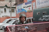 An Indian paramilitary soldier stands guard at the entrance of Press Enclave, which houses several newspaper offices, in Srinagar, Indian-controlled Kashmir, Wednesday, Sept. 8, 2021. Police raided the homes of four journalists on Wednesday, triggering concerns of a further crackdown on press freedom in the disputed region. After the raids in Srinagar, the region's main city, the four journalists were summoned to local police stations where they were questioned. Police did not specify the reason for the raids. (AP Photo/Mukhtar Khan)