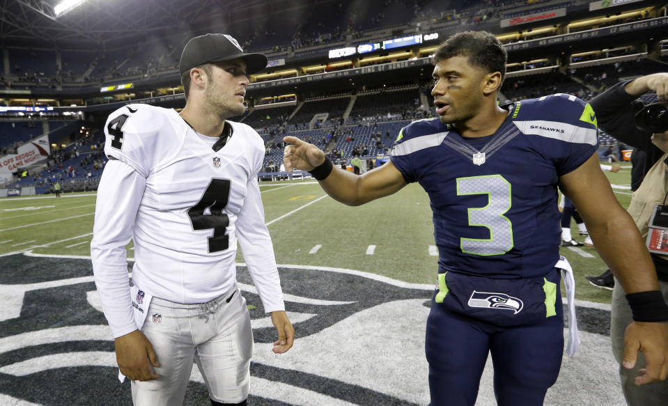 Seattle Seahawks quarterback Russell Wilson (3) and Oakland Raiders quarterback Derek Carr (4) talk on the field following a preseason NFL football game, Thursday, Sept. 3, 2015, in Seattle. The Seahawks beat the Raiders 31-21. (AP Photo/Elaine Thompson)