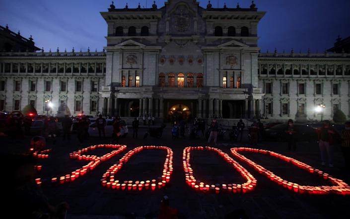 In front of the National Palace in Guatemala City, Guatemala, an candle-lit vigil is held for the country's 9,000 Covid victims - REUTERS