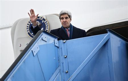 U.S. Secretary of State Kerry waves while boarding his plane at Franz-Josef-Strauss Airport in Munich