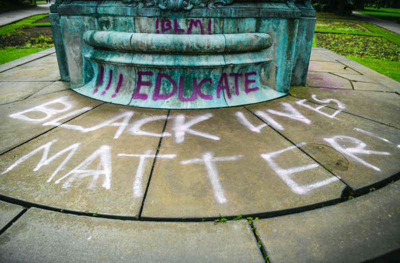 The statue was daubed with 'Black Lives Matter' and 'educate'. (SWNS)