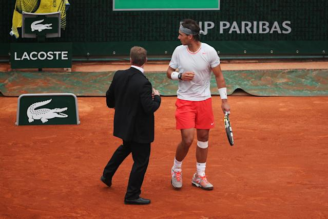 PARIS, FRANCE - JUNE 09: Rafael Nadal of Spain is ushered away by a security guard after a protester lit a flare and jumped onto the court during the Men's Singles final match against David Ferrer of Spain on day fifteen of the French Open at Roland Garros on June 9, 2013 in Paris, France. (Photo by Clive Brunskill/Getty Images)