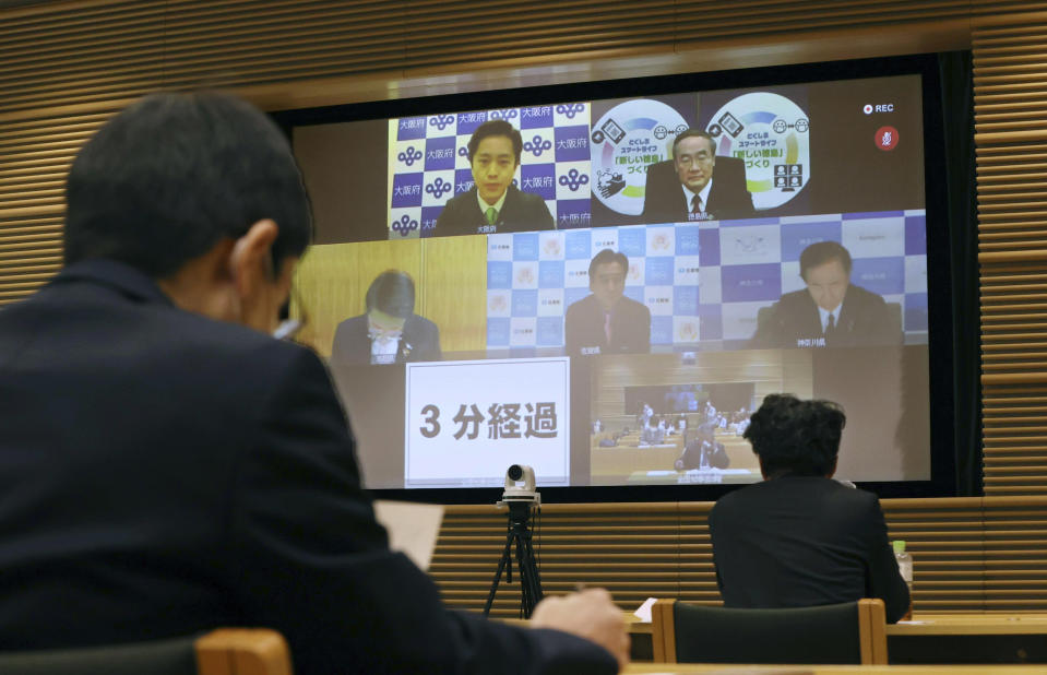 A screen shows Osaka Gov. Hirofumi Yoshimura, top left, speak during an online meeting of the National Governors' Association ahead of the start of stronger measures to prevent the spread of the coronavirus, in Tokyo Sunday, April 4, 2021. Semi-emergency coronavirus measures began in Osaka and its neighboring prefecture in western Japan and another prefecture in the north Monday, April 5, 2021, as Japan tries to minimize the economic impact to specific areas where infections are rising back less than four months before the Tokyo Olympics. (Satoru Yonemaru/Kyodo News via AP)