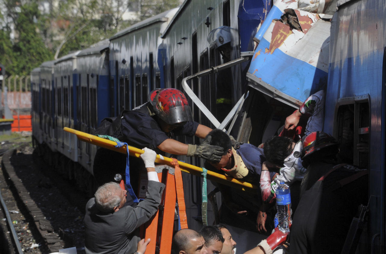 Firemen rescue wounded passengers from a commuter train after a collision in Buenos Aires, Argentina, Wednesday Feb. 22, 2012. A packed train slammed into the end of the line in Buenos Aires' busy Once station Wednesday, injuring over 300 morning commuters, Argentina's transportation secretary said. (AP Photo/Leonardo Zavattaro,Telam)