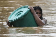 A man uses a plastic canister to float while negotiating rising floodwaters from Typhoon Vamco in Marikina, Philippines, on Thursday, Nov. 12, 2020. Vamco swelled rivers and flooded low-lying areas as it passed over the storm-battered northeastern part of the country, where rescuers were deployed early Thursday to help people flee the rising waters. (AP Photo/Aaron Favila)