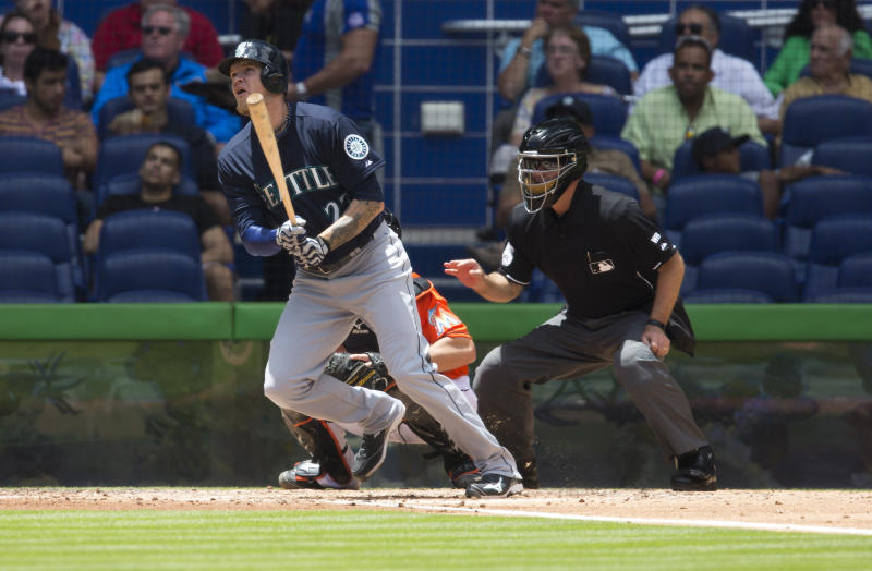 Seattle Mariners batter Corey Hall hits a scarifice fly to center field and advances a runner from second to third base during the fourth inning of a baseball game in Miami, Sunday, April 20,2014 against the Miami Marlins as home plate umpire Ed Hickox watches. (AP Photo/J Pat Carter)