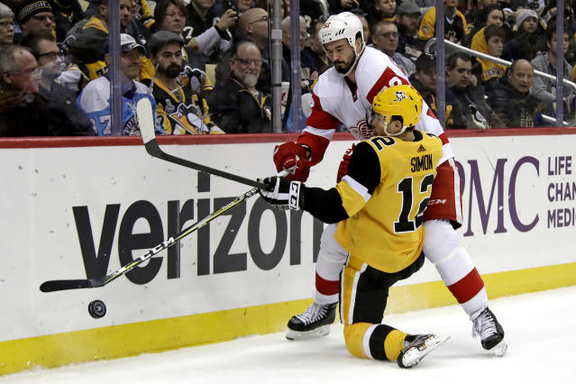 Pittsburgh Penguins' Dominik Simon (12) is checked off the puck by Detroit Red Wings' Jonathan Ericsson (52) during the second period of an NHL hockey game in Pittsburgh, Thursday, Dec. 27, 2018. (AP Photo/Gene J. Puskar)