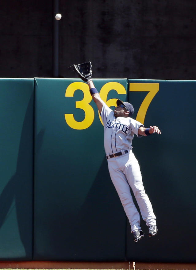 Seattle Mariners right fielder Endy Chavez leaps but can't catch a home run ball from Oakland Athletics' Adam Dunn during the first inning of a baseball game on Monday, Sept. 1, 2014, in Oakland, Calif. (AP Photo/Marcio Jose Sanchez)