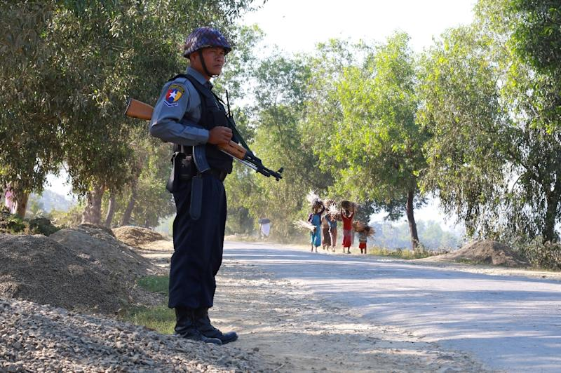 An armed Myanmar police officer is posted on the road during the arrival of the UN special rapporteur on Myanmar in Buthidaung to visit areas of northern Rakhine State on January 14, 2017