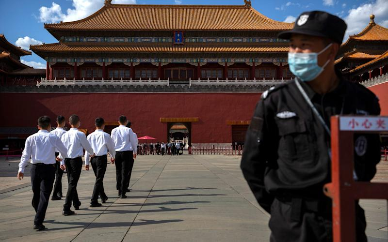 A security officer stands guard as plainclothes personnel march in formation outside the entrance to the Forbidden City in Beijing - AP Photo/Mark Schiefelbein