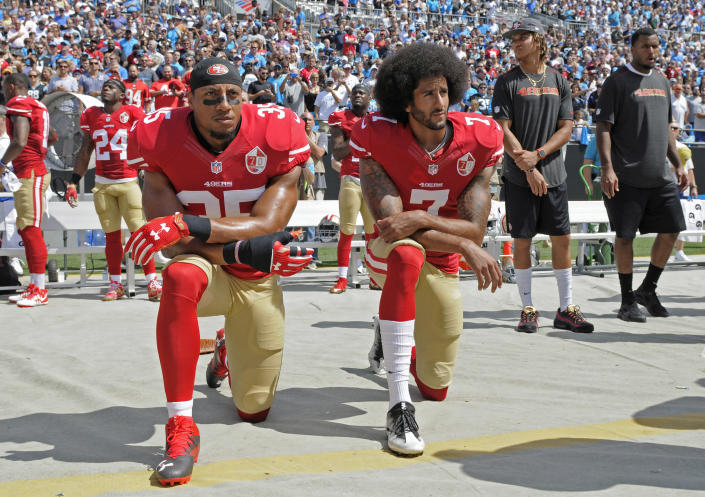 FILE - In this Sept. 18, 2016, file photo, San Francisco 49ers' Colin Kaepernick (7) and Eric Reid (35) kneel during the national anthem before an NFL football game against the Carolina Panthers in Charlotte, N.C. Four years after Kaepernick spoke out against racism and eventually lost his job for peacefully protesting, the NFL supports his fight and now encourages players to stand up for racial equality and social justice.(AP Photo/Mike McCarn, File)