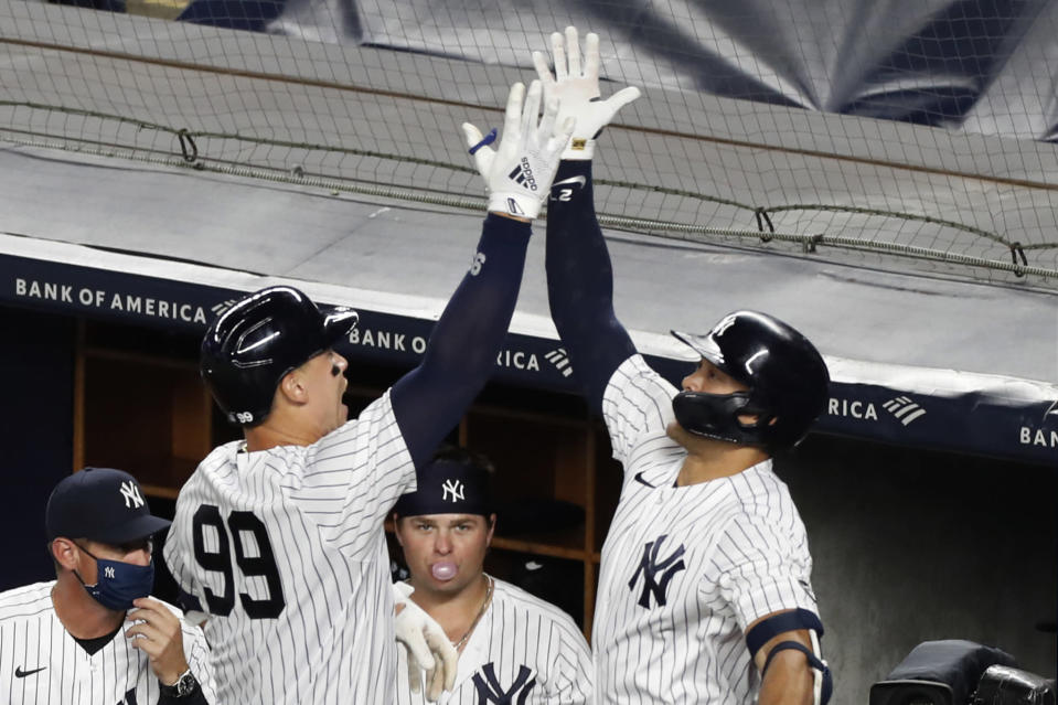 New York Yankees' Aaron Judge (99) celebrates with Giancarlo Stanton after hitting a two-run, home run in the eighth inning of a baseball game against the Boston Red Sox, Sunday, Aug. 2, 2020, at Yankee Stadium in New York. First baseman Luke Voit, blows a bubble as he watches the two celebrate. (AP Photo/Kathy Willens)
