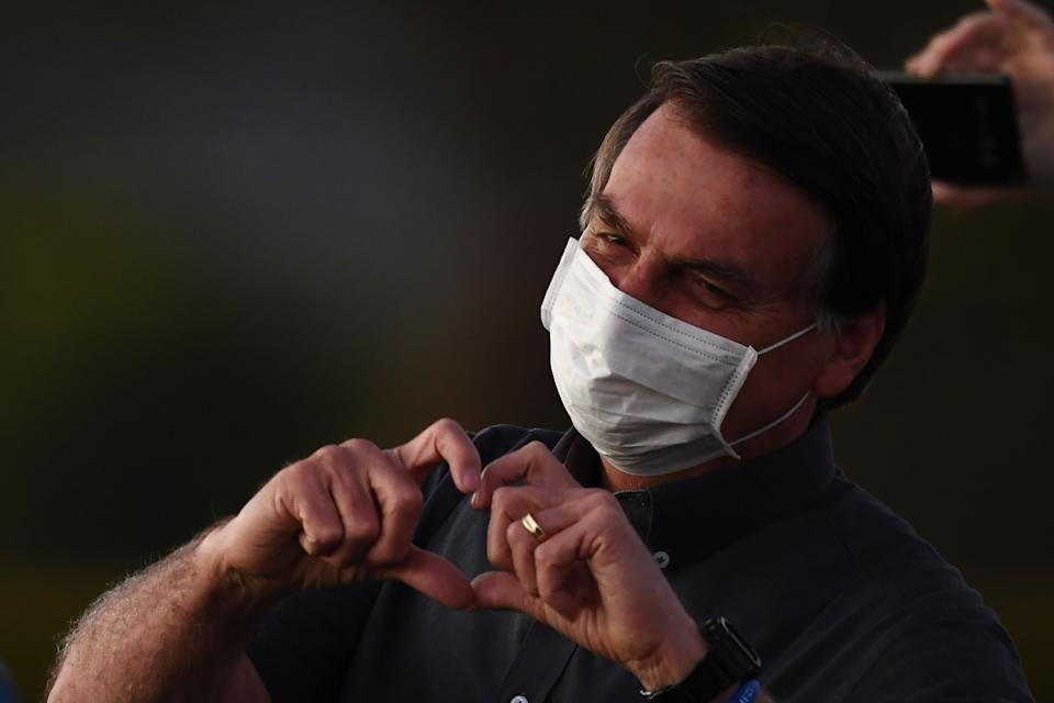 Brazilian President Jair Bolsonaro makes a heart's shape with his hands to supporters from the Alvorada Palace in Brasilia, on July 20, 2020, amid the new coronavirus pandemic. (Photo by EVARISTO SA / AFP) (Photo by EVARISTO SA/AFP via Getty Images)