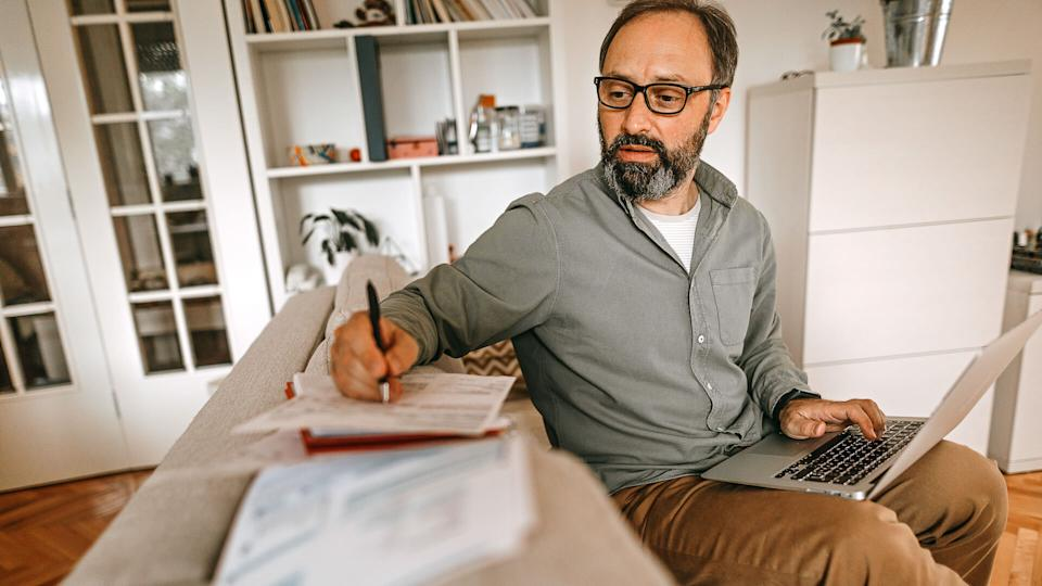 Mature man sitting on sofa in living room with laptop and financial reports, doing his monthly budget.