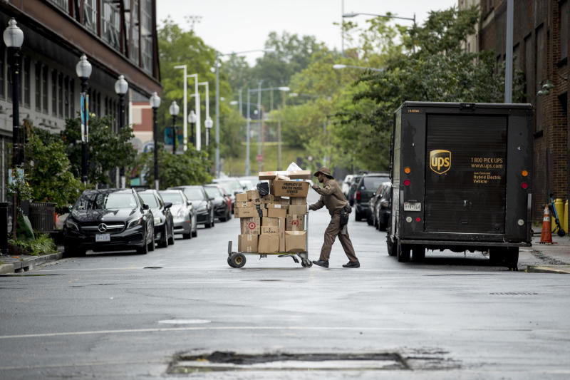 """In this May 22, 2020, photo, a delivery man pushes a cart full of packages to deliver to an apartment building on an almost empty street in the Shaw neighborhood of Washington. As a candidate for the White House, President Donald Trump once said he wanted """"whatever is best"""" for the residents of the nation's capital. But over the course of his more than three years in office a disconnect between the president and District of Columbia has emerged -- a chasm that has only grown during the coronavirus pandemic. (AP Photo/Andrew Harnik)"""