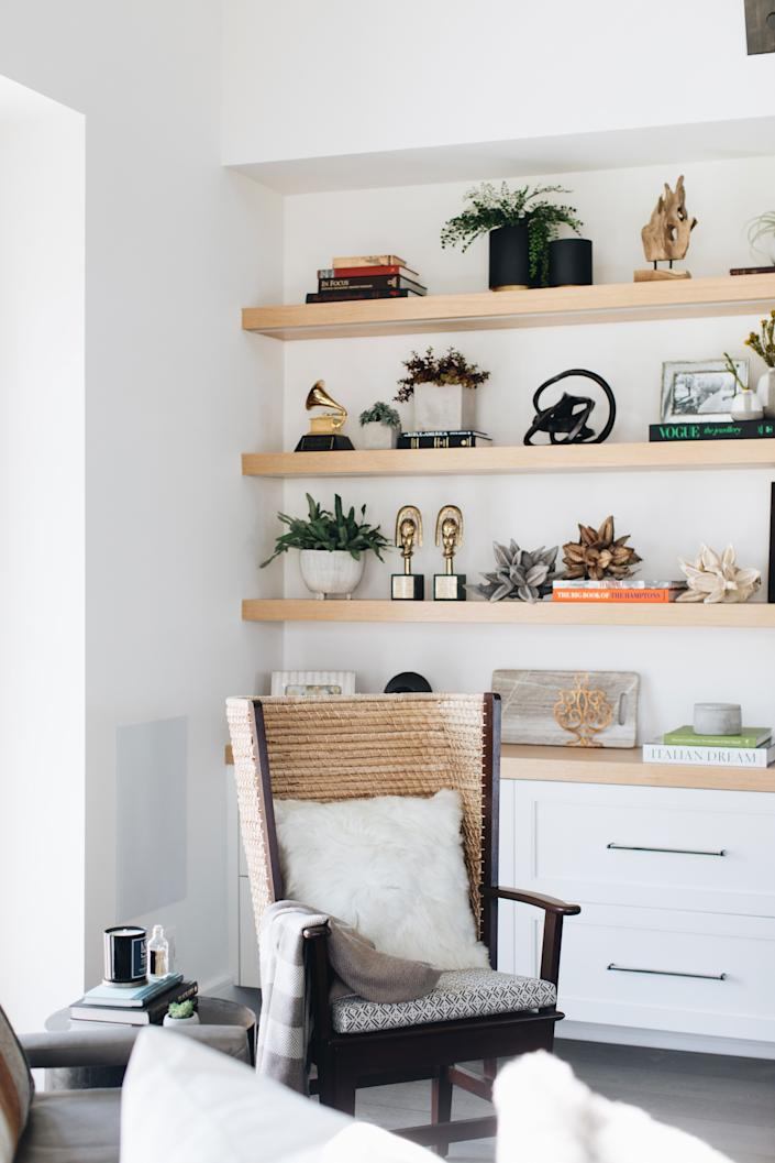 """<div class=""""caption""""> Headley's awards (including her Grammy) share shelf space with a collection of books, planters, star pods, and sculpture from <a href=""""https://amystormandco.com/"""" rel=""""nofollow noopener"""" target=""""_blank"""" data-ylk=""""slk:Amy Storm & Company"""" class=""""link rapid-noclick-resp"""">Amy Storm & Company</a>. </div>"""