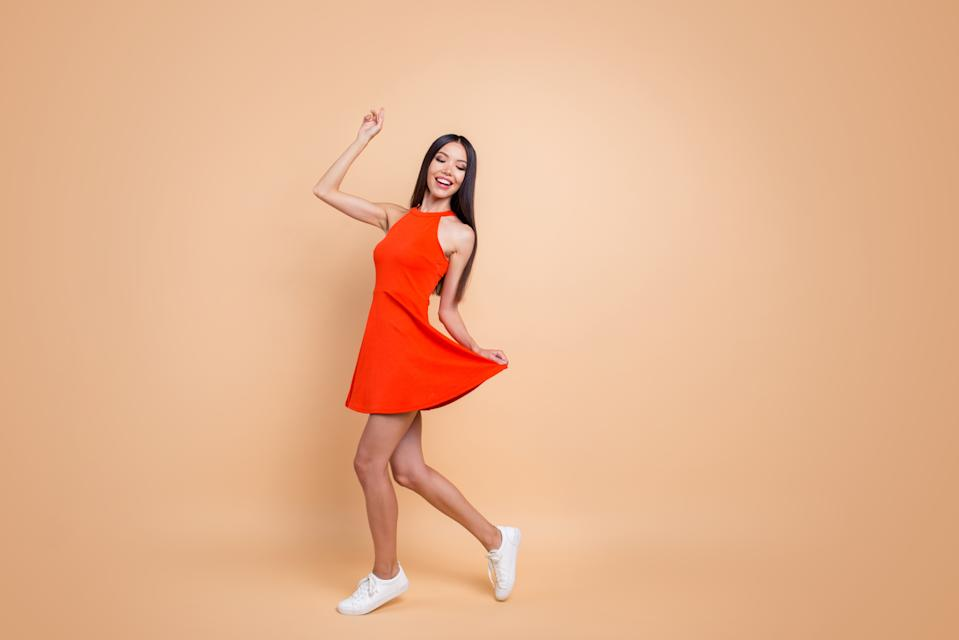 Full length size studio photo portrait of beautiful charming good mood toothy beaming smile tender careless carefree cheerful gorgeous korean teen lady holding skirt isolated pastel beige background