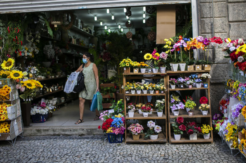 RIO DE JANEIRO, BRAZIL - JUNE 08: A woman wearing a mask leaves a flower shop in the Saara commercial center on the first monday of quarantine relaxing in the city amidst the coronavirus (COVID-19) pandemic on June 8, 2020 in Rio de Janeiro, Brazil. A decree signed by Governor Wilson Witzel established the easing of social isolation in the state of Rio de Janeiro, with partial reopening of bars, restaurants and shopping malls. The return of football and other high-performance sports is also authorized by the government. (Photo by Bruna Prado/Getty Images)