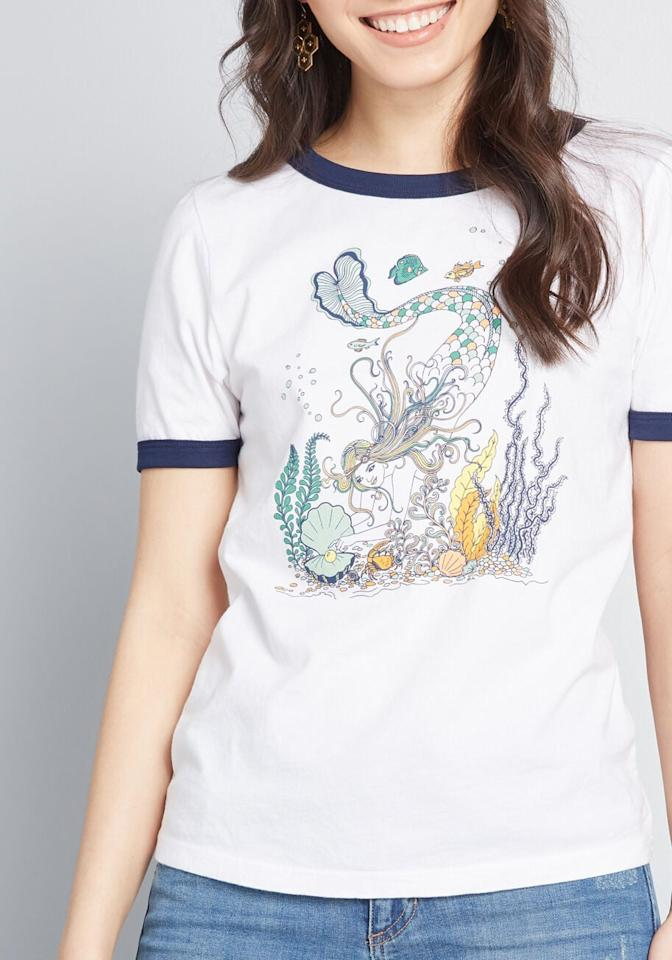 """<p>We love the illustration on this <a href=""""https://www.popsugar.com/buy/ModCloth-x-Dupenny-Undersea-Queen-Mermaid-Graphic-Tee-510555?p_name=ModCloth%20x%20Dupenny%20Undersea%20Queen%20Mermaid%20Graphic%20Tee&retailer=modcloth.com&pid=510555&price=30&evar1=tres%3Aus&evar9=36125657&evar98=https%3A%2F%2Fwww.popsugar.com%2Flove%2Fphoto-gallery%2F36125657%2Fimage%2F46841213%2FModCloth-x-Dupenny-Undersea-Queen-Mermaid-Graphic-Tee&list1=gifts%2Choliday%2Cchristmas%2Cgift%20guide%2Cdisney%2Cthe%20little%20mermaid%2Cmermaids%2Cnostalgia%2Cgifts%20for%20women&prop13=mobile&pdata=1"""" rel=""""nofollow"""" data-shoppable-link=""""1"""" target=""""_blank"""" class=""""ga-track"""" data-ga-category=""""Related"""" data-ga-label=""""https://www.modcloth.com/shop/tops/modcloth-x-dupenny-undersea-queen-mermaid-graphic-tee-in-white/164784.html"""" data-ga-action=""""In-Line Links"""">ModCloth x Dupenny Undersea Queen Mermaid Graphic Tee</a> ($30).</p>"""