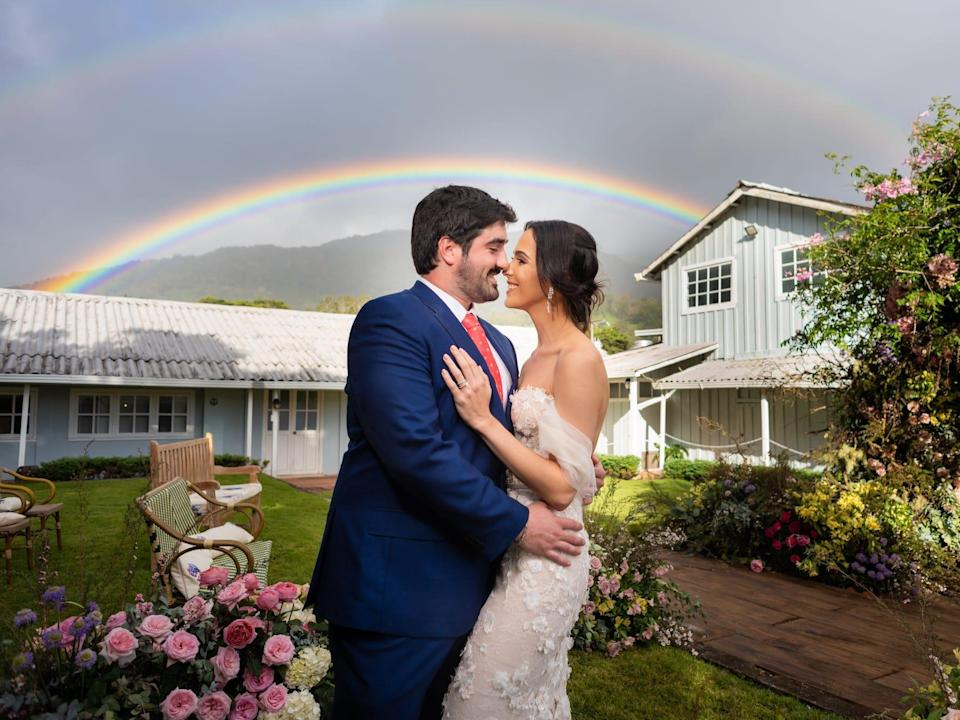 A bride and groom embrace with a rainbow behind them.