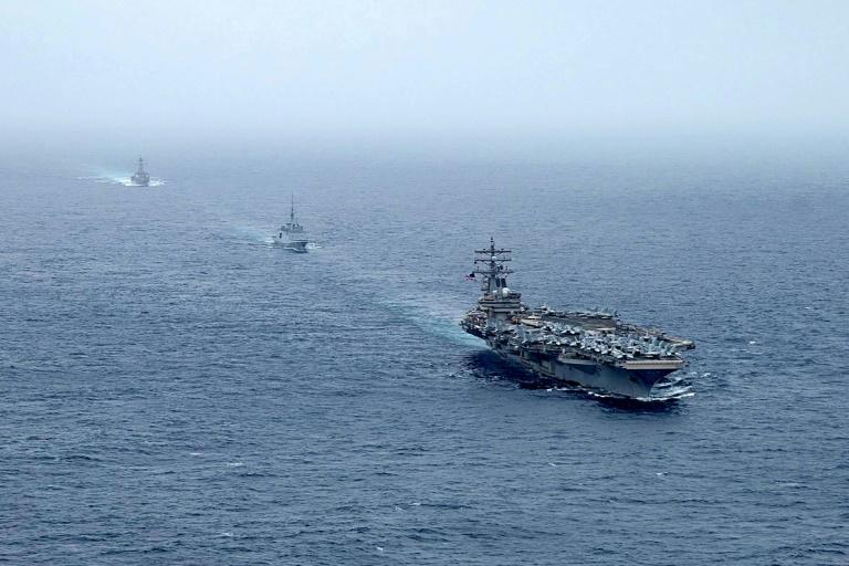 A handout photo courtesy of the US Navy's Twitter account on July 25, 2021 shows aircraft carrier USS Ronald Reagan, French navy frigate FS Languedoc, and guided-missile destroyer USS Halsey at sail in the Arabian Sea
